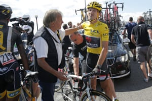 Fabian Cancellara, wearing the overall leader's yellow jersey, gets back on his bicycle after crashing