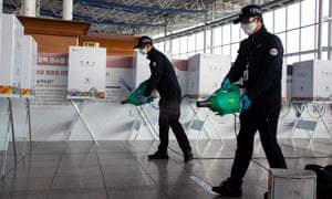 Workers spray disinfectant as a precaution against the coronavirus outbreak at a polling station in Seoul, South Korea, 9 April 2020.