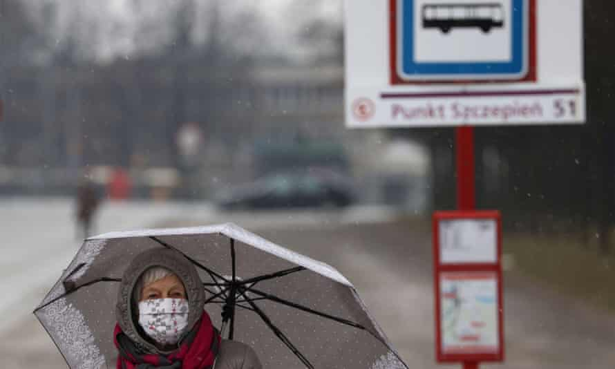 A woman wearing a face mask walks past a temporary bus stop for Covid vaccination patients in Warsaw, Poland.