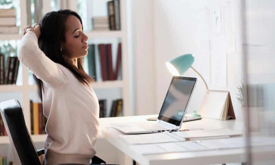 A woman stretches at a desk