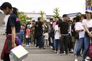 Local residents queue for water in Atsuma
