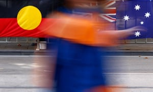 A person walks past the Aboriginal and Australian flags