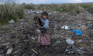 A child walks on the trash strewn shore of Lake Titicaca