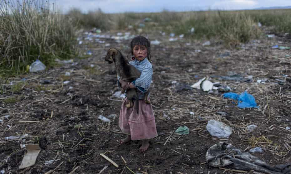 A child walks on the trash strewn shore of Lake Titicaca