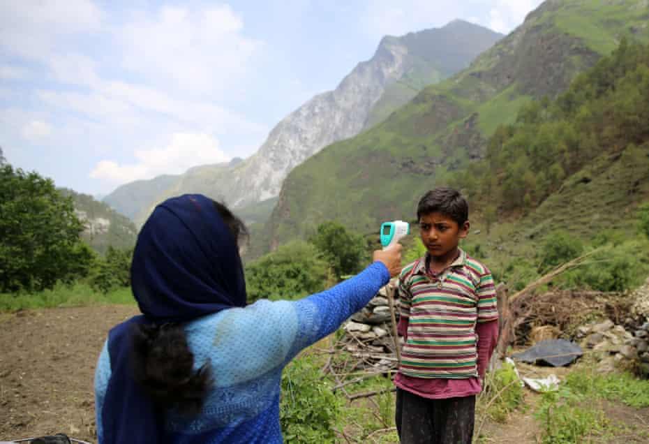 A boy has his temperature checked by a community health worker in Durmi village, Uttarakhand.