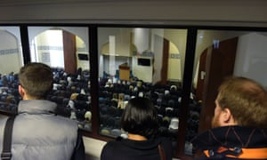 Visitors watch worshippers in East London Mosque.