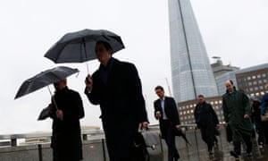 Workers crossing London Bridge in London.