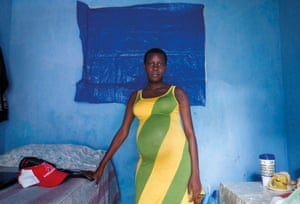 Wideline, from Port-au-Prince, Haiti, standing against a blue wall by a bed, one of a series of self-portraits by people living with HIV