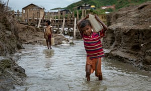A 10-year-old boy from Myanmar collects water at a camp in Cox's Bazar, Bangladesh