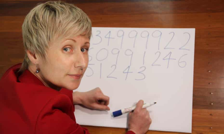 Anastasia Woolmer writing the digits of pi on a large piece of cardboard