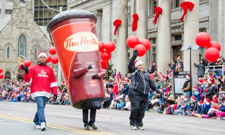 A large cup of Tim Hortons coffee marches in the Santa Claus parade in Toronto, Ontario.