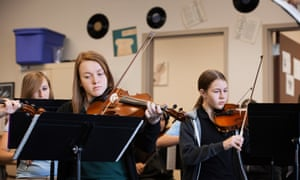 Girls playing violin in music class