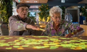 Lights are projected on to a table as two people with dementia use Tovertafel (Magic Table).