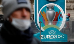 A person wearing a face mask walks past the Euro 2020 countdown clock in St Petersburg