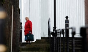An elderly woman walks in Stockport town centre.