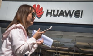 A woman walks past a Huawei store in Beijing, China, after Google halted business with the Chinese phonemaker.