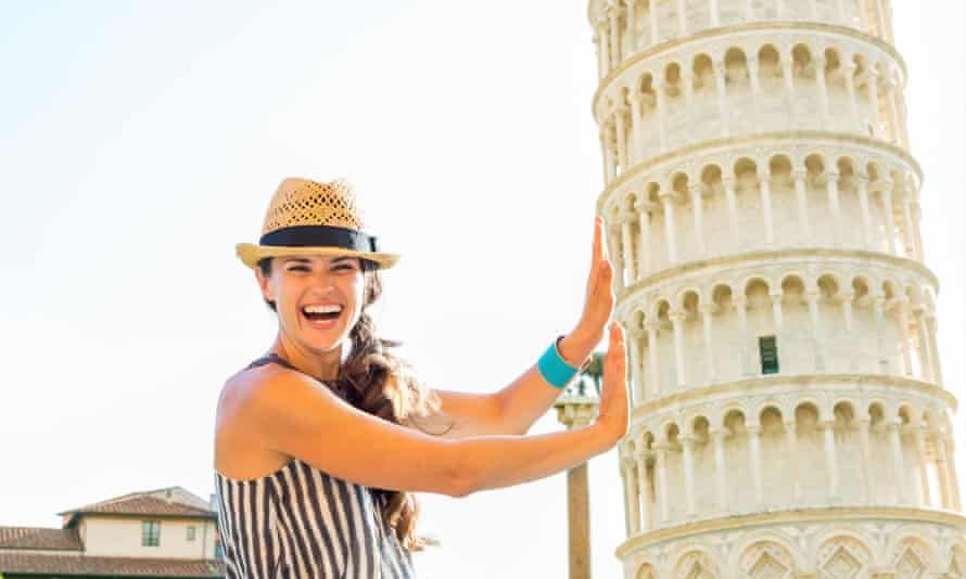 funny young woman supporting leaning tower of pisa, tuscany, italyFunny young woman supporting leaning tower of pisa, tuscany, italy
