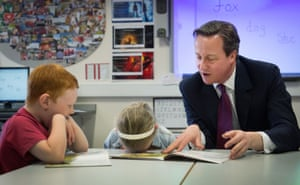 David Cameron helps pupils with a reading lesson