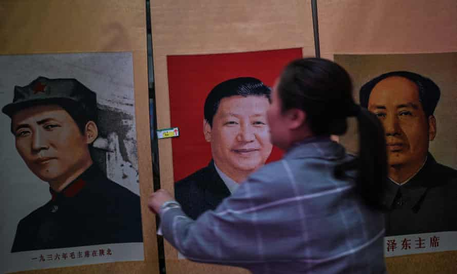 A stall vendor holding a portrait of Xi Jinping next to pictures of the former Chinese leader Mao Zedong at Dongfanghong theatre in Yan'an.