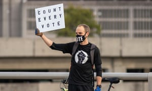 "A protester in Atlanta holds a sign asking officials to ""count every vote""."