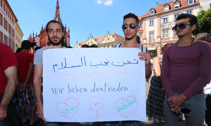 Refugees, some of whom come from Syria, hold a sign saying 'We love peace' in Würzburg on 20 July.