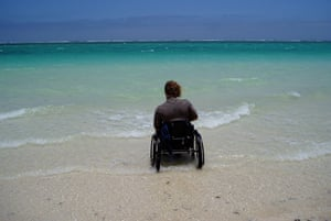 Kevin Hayley in a wheelchair facing the ocean