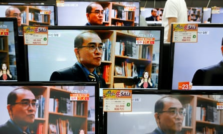 A customer in Seoul watches TV sets broadcasting a news report on Thae Yong ho, who defected with his family to South Korea.
