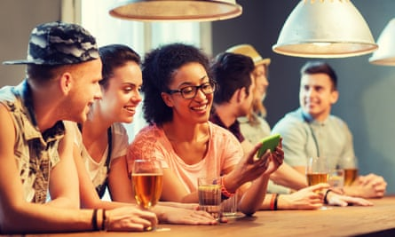 Young people in a bar looking at a smartphone