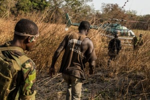 Two suspected poachers arrested deep in the Chinko bush are escorted to a helicopter, which will fly back to base. There, the men will be questioned in a holding cell.
