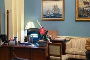 A man wearing a pro-Trump hay sits at a desk after invading the building