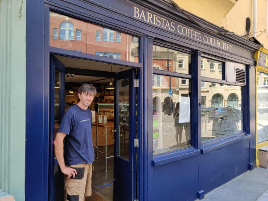 George Martin of the Barista Coffee Collective in his shop doorway, dressed in shorts and a blue T-shirt