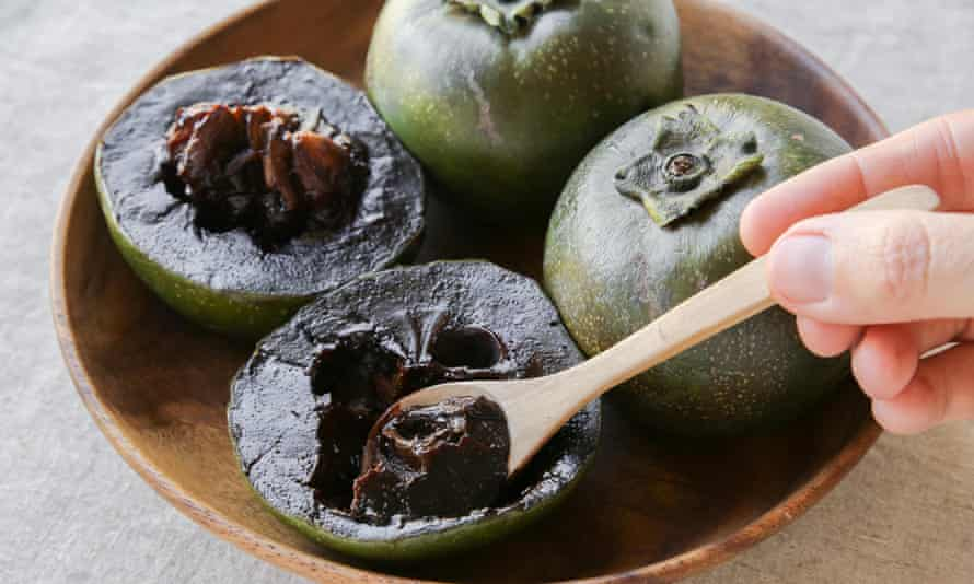 Black sapote chocolate pudding fruit on a wooden plate.