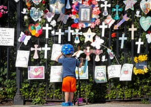 A child looks at a memorial to Covid victims at the Green-Wood cemetery in Brooklyn, as the US death toll is expected to surpass 600,000