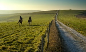 Two horses and riders on an early morning walk across the South Downs National Park, Lewes.