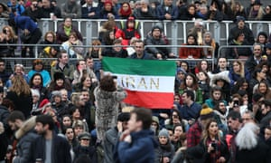 A man holds up an Iranian flag as people gather in Trafalgar Square for the public screening of The Salesman.