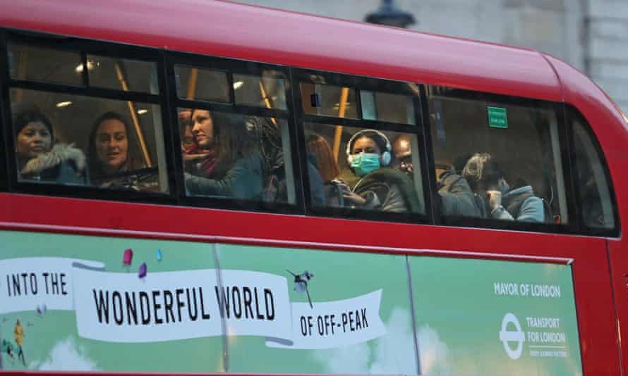 A woman wearing a face mask on a bus in London