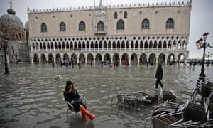 A woman sits in a flooded St. Mark's Square.
