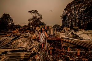 """Weeks after the fire, under the sky blanketed by smoke coming from the nearby Howe Range, Jess Van Swol stands in her devastated property. The house has gone but the large Eucalypt that has housed families of koalas survived. """"I am full of mixed emotion- on one side I am devastated for the habitat, my home and the town around me - but on the other I have optimism for what lies ahead."""""""