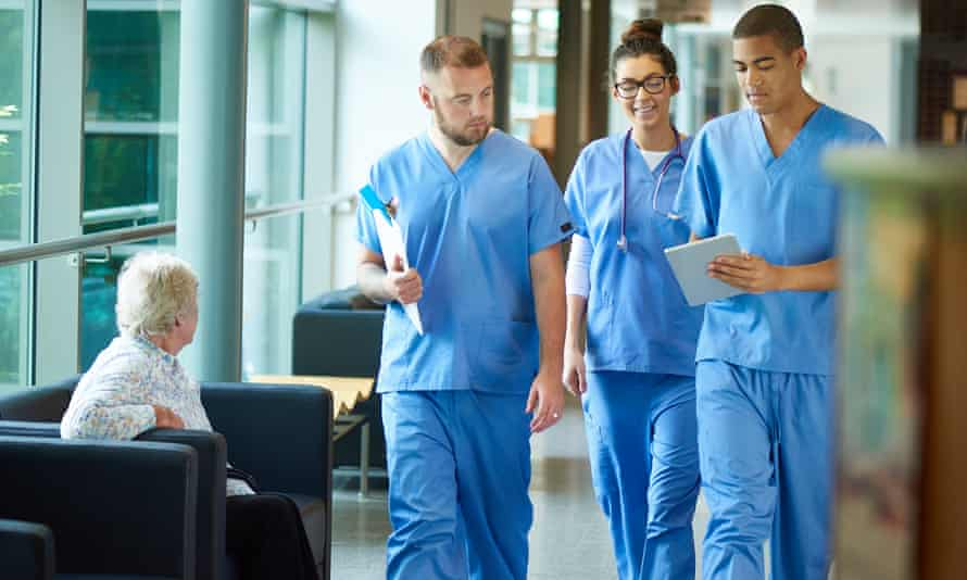 Three junior doctors in blue uniform walk down a hospital corridor
