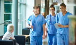 junior doctors walking along a hospital corridor discussing case and wearing scrubs. A patient or visitor is sitting in the corridor as they walk past .