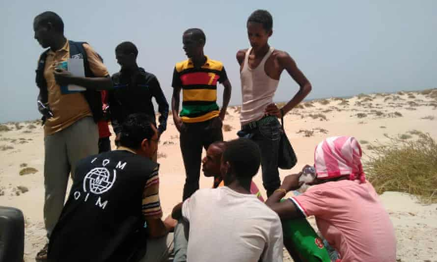 A group of Somali and Ethiopian people wait on a beach near Shabwa after being forced from a boat off the coast of Yemen.