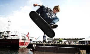 A skater is doing tricks on his skate board at a half pipe ramp in the harbor of Copenhagen