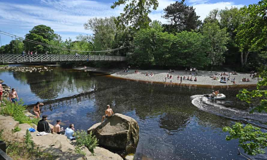 People sunbathing and paddling in the River Wharfe in Ilkley in June