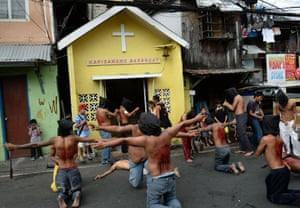 Penitents flagellate themselves as part of Lenten observance along a street in Manila, Phillipines