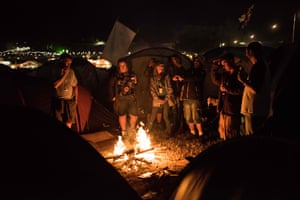 Festival-goers congregate around a fire adjacent to their tents