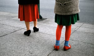Red Stockings, 1961, by Fred Herzog. It is the colour tones that entrance. In this instance, the deep red of the woman's pleated dress is echoed in the girl's tights and shoes.