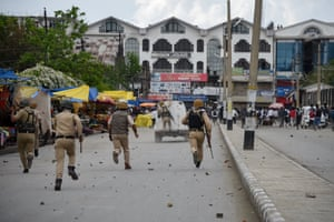 Srinagar, India. Policemen chase Kashmiri students after clashes during a protest following the alleged rape of a child in the region