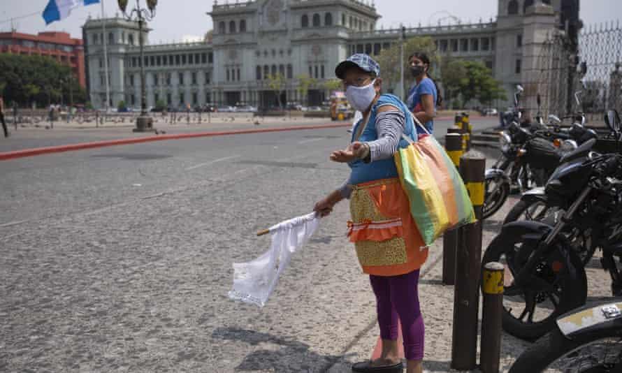 Gladys Serrano, 60, wearing a mask against the spread of the new coronavirus, shows a white flag while standing at Constitution Square in Guatemala City on 4 May.