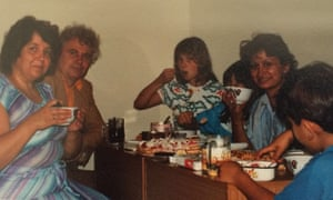 Writer Dina Nayeri (hidden) and her mother (holding cup) having tea with a family of Russian refugees at hotel Barba refugee camp near Rome in 1989