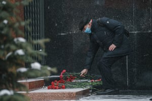 A man lays flowers at the mausoleum